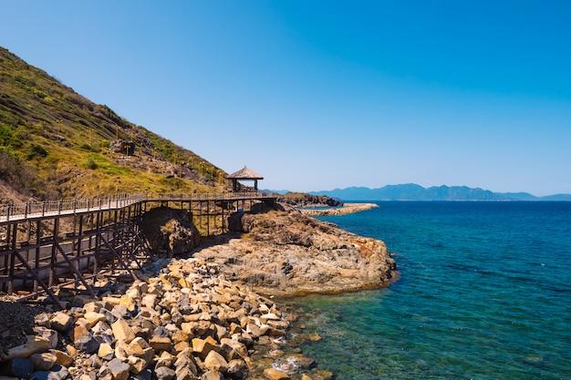Скалистый остров с деревянным мостом возле океана Premium Фотографии