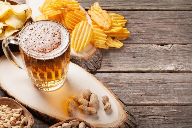 ラガービールジョッキと木製のテーブルの上の軽食 Premium写真