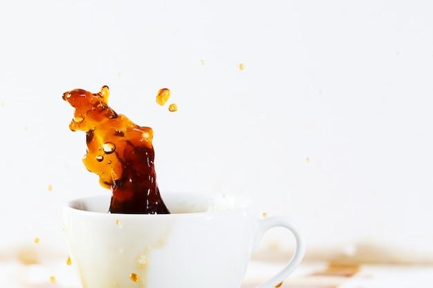 美しいスプラッシュを作成するこぼれるコーヒーのカップ Premium写真