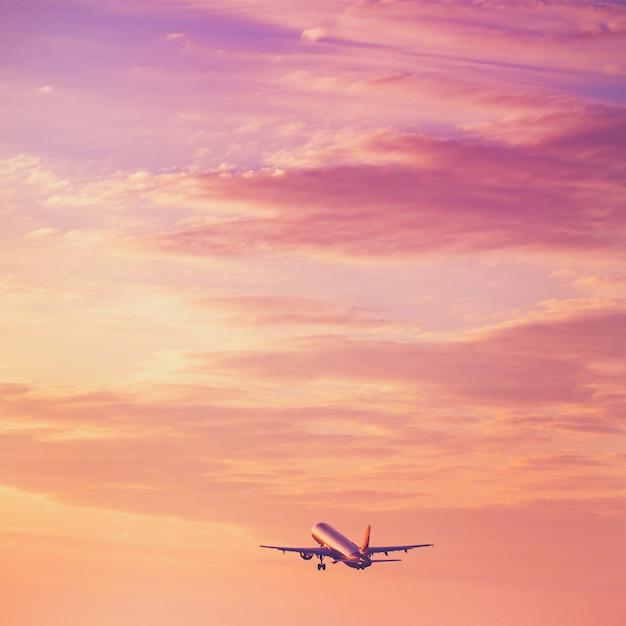 夕焼け空で離陸する飛行機 Premium写真