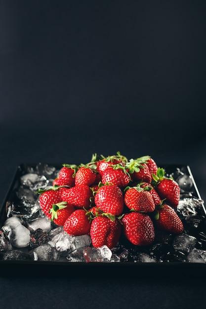 氷の上で熟したイチゴ果実 Premium写真