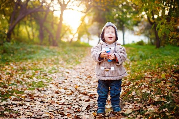 Счастливый малыш смеется и гуляет в парке Premium Фотографии