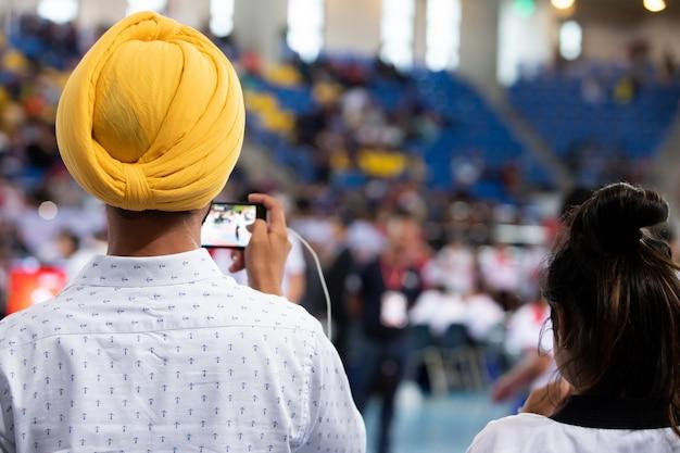 インドのシーク教徒の男黄色の頭ターバンターンバックビュースマートフォンを使用してスポーツ競技の撮影を記録します。 Premium写真
