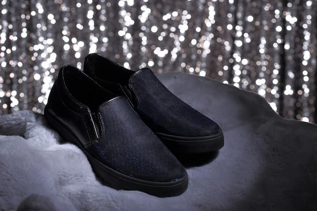 毛皮と銀の壁紙に黒い靴 Premium写真
