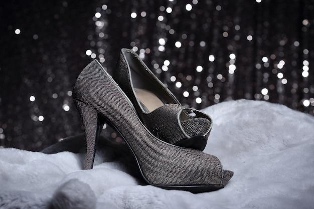 毛皮と銀の壁紙にハイヒールの靴 Premium写真