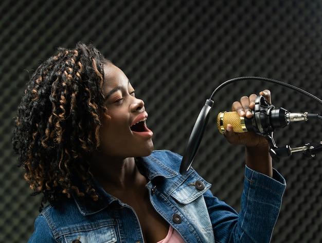 アフリカのティーンエイジャーの女性アフロ髪歌を歌う Premium写真