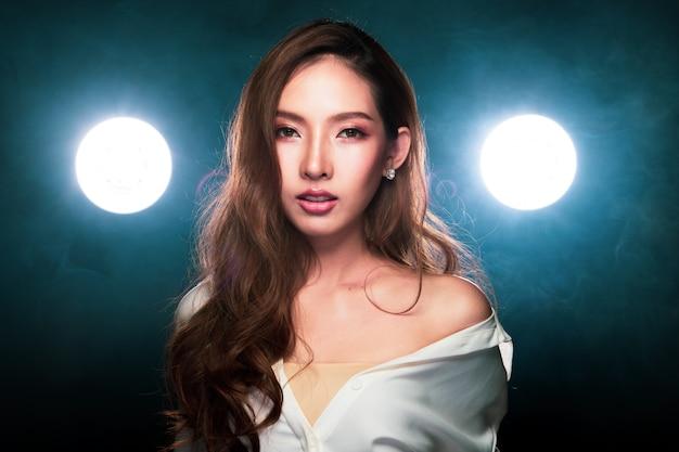 アジアの女性は、飛行を投げるブロンドの髪スタイルをカールします。 Premium写真