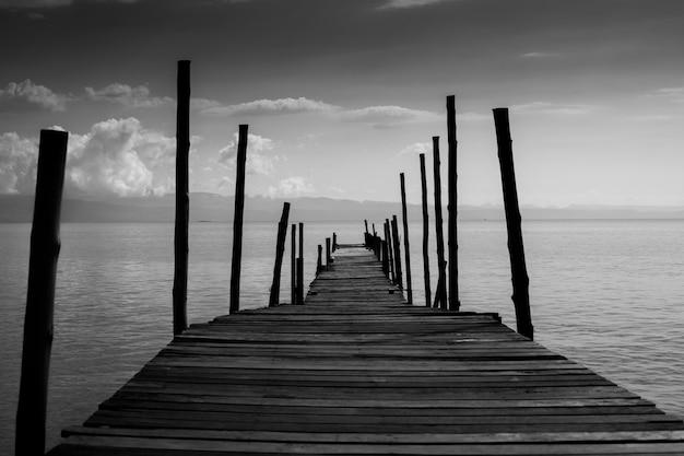 古い木造の橋は海への道を渡る。 Premium写真