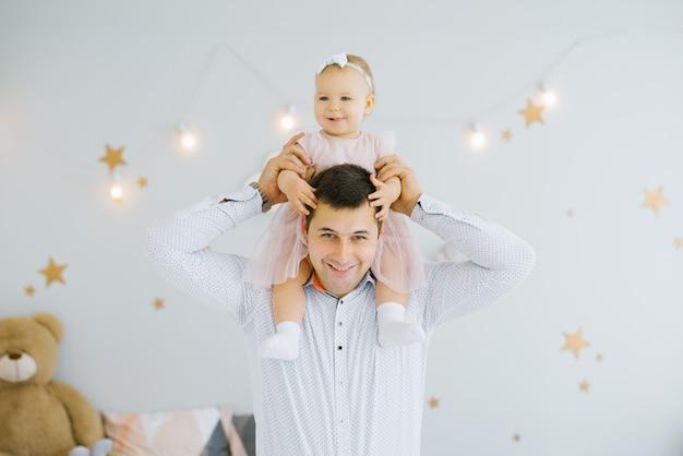 Счастливый малыш годовалой девочки сидит на плечах папы и улыбаются в детской комнате, украшенной светящимися звездами на стенах Premium Фотографии