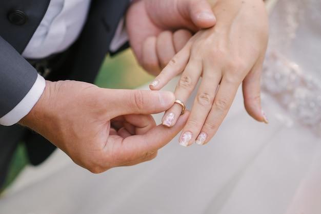 新郎は指輪の結婚式の花嫁を着ます。 Premium写真