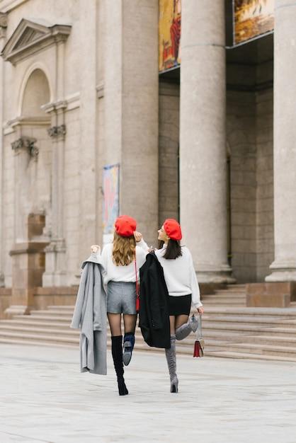 赤いベレー帽のガールフレンドは、街を歩き回り、歩き、笑い、人生を楽しみます。 Premium写真