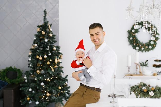 Счастливый отец держит своего маленького сына в костюме санта или шляпу на руках в гостиной возле елки. с новым годом дома Premium Фотографии