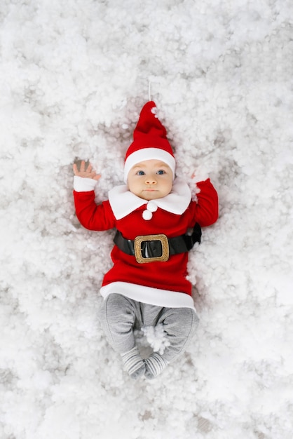 サンタの衣装で面白い少年はクリスマスと新年を祝う準備ができています。クリスマスカード Premium写真