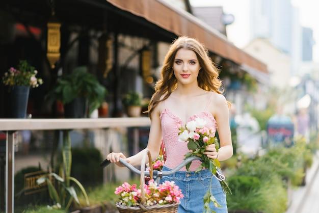 夕日を浴びて街の通りにきれいで美しい少女の肖像画。女の子はバラの花束を持ち、自転車のハンドルバーを持っています。夏の散歩のコンセプト Premium写真