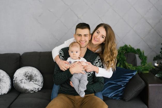Портрет красивой молодой семьи с маленьким ребенком сидит на диване в гостиной и улыбается Premium Фотографии