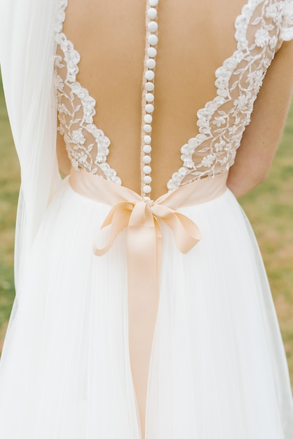 Красивое свадебное платье без спинки с большим количеством пуговиц и бежевым бантом Premium Фотографии