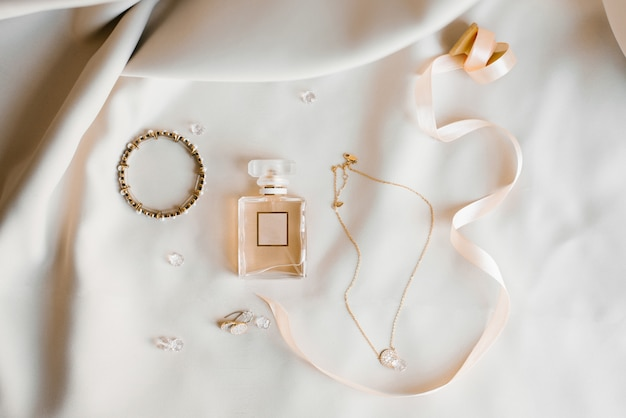 Аксессуары невесты: туалетная вода, серьги, кулон и браслет. утренние невесты. Premium Фотографии