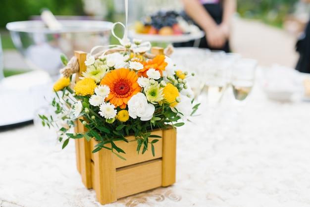 Яркая цветочная композиция из белых, желтых и оранжевых цветов хризантемы в деревянной коробке Premium Фотографии