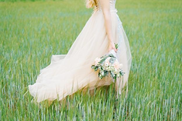 Красивый нежный свадебный букет в деревенском стиле с белой лентой в руках Premium Фотографии