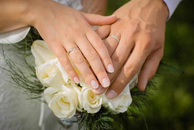 Руки жениха и невесты с обручальными кольцами на свадебный букет из белых роз Premium Фотографии