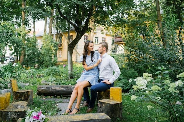 愛の幸せなカップルの男と夏の日にベンチに座っている女の子で美しい。 Premium写真
