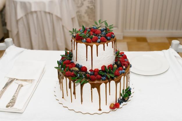 Белый двухуровневый свадебный торт с ягодами и ганашем Premium Фотографии