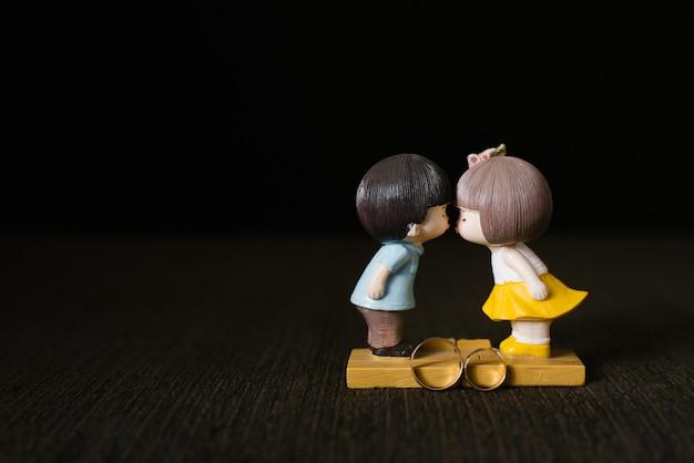 Статуэтка целования парня и девушки и золотые обручальные кольца на коричневом фоне Premium Фотографии