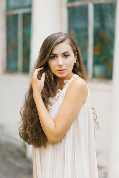 Красивая славянская девушка с длинными волнистыми волосами в бежевом романтическом платье держит руку в волосах Premium Фотографии