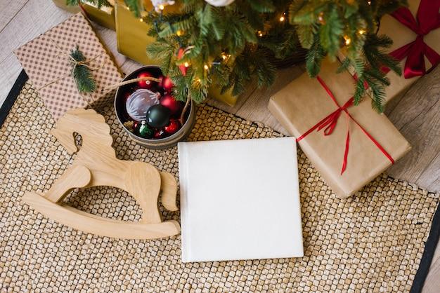 クリスマスプレゼントに囲まれたクリスマスツリーの下の白い革製のカバー、結婚式、または家族のフォトアルバムの写真集 Premium写真