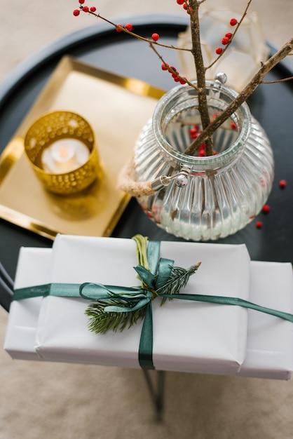 クリスマスプレゼントとクリスマスと新年のために飾られたリビングルームのコーヒーテーブルの上の赤い果実の枝と花瓶 Premium写真