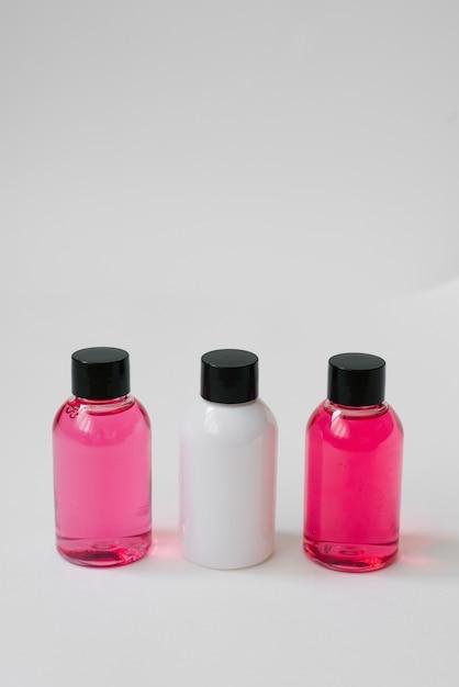 ボディケア化粧品や白い背景の上の髪とピンクと白の色のミニボトル Premium写真