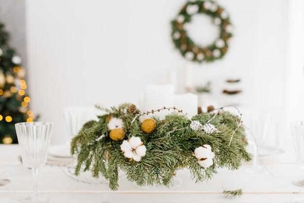 Новогодняя композиция из ели, хлопка, грецкого ореха на праздничном столе Premium Фотографии