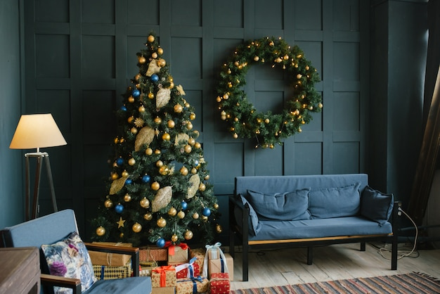 ロフトスタイルのリビングルームの壁に枕とクリスマスリースと青いソファ。 Premium写真
