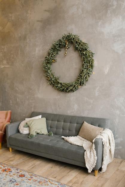 壁にあるソファの上にある枕付きのグレーのソファには、クリスマスリースが飾られています。リビングルームでのスカンジナビアスタイル Premium写真