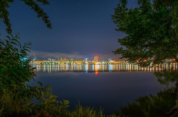 広く穏やかな川の夜の街の反射。 Premium写真