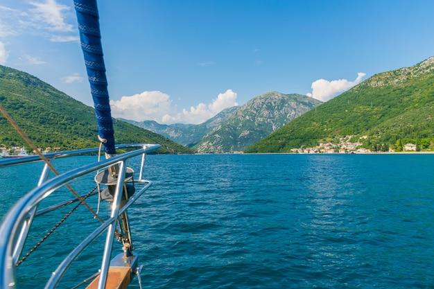 モンテネグロの美しいコトル湾に沿って豪華ヨットが航行します。 Premium写真