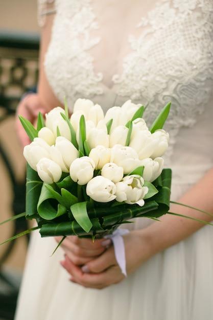結婚式の日のブライダルブーケ。白いチューリップの花束を持って美しい少女。 Premium写真