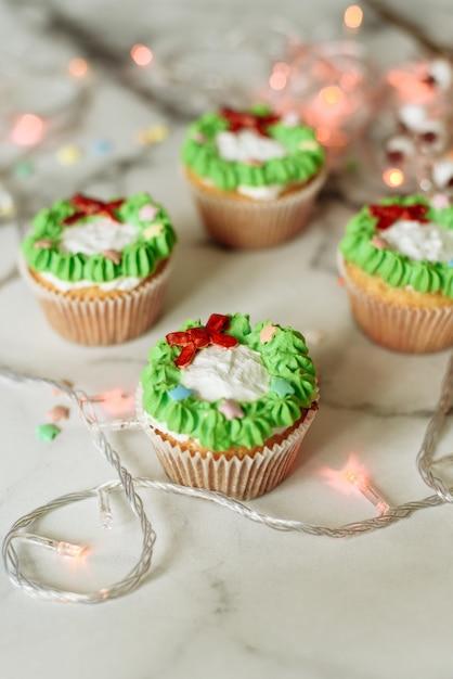 Новогодние сладости на мраморном столе. рождественские кексы украшенные мастикой и сливками Premium Фотографии