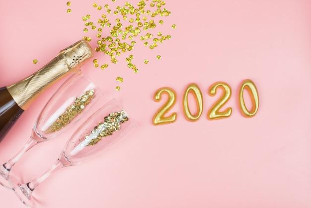 シャンパンのボトル、金色の紙吹雪とピンクのパステルにゴールドの番号を持つ透明なメガネ Premium写真