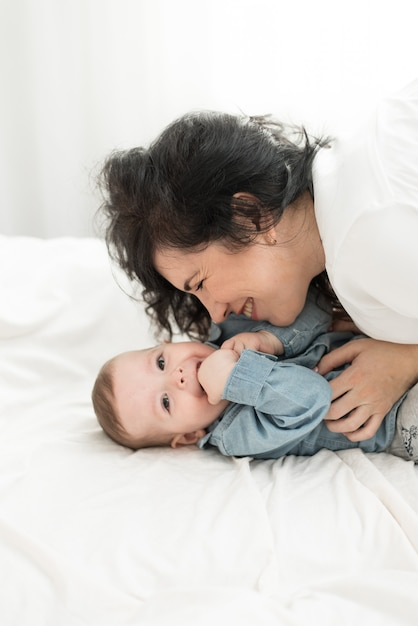 母はベッドで赤ちゃんと遊ぶ。母は息子をくすぐります。 Premium写真