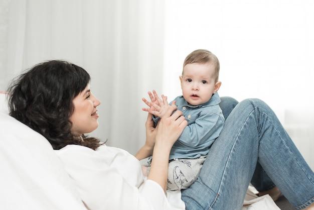 Веселые игры с годовалым малышом мамы. счастливая семья в доме Premium Фотографии