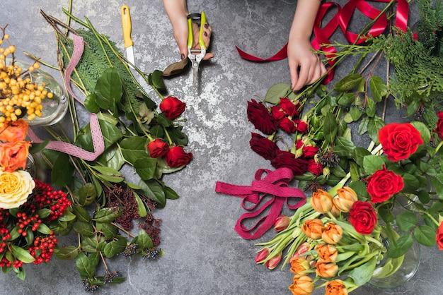Флорист создает букет в цветочном магазине. вид сверху на создание букета из красных, оранжевых, бордовых, желтых роз, тюльпанов. Premium Фотографии