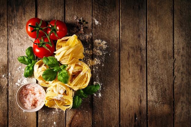 新鮮なバジルとトマトのパスタタリアテッレを調理するためのおいしいフレッシュカラフルな材料。上面図。木製テーブルの背景。 無料写真