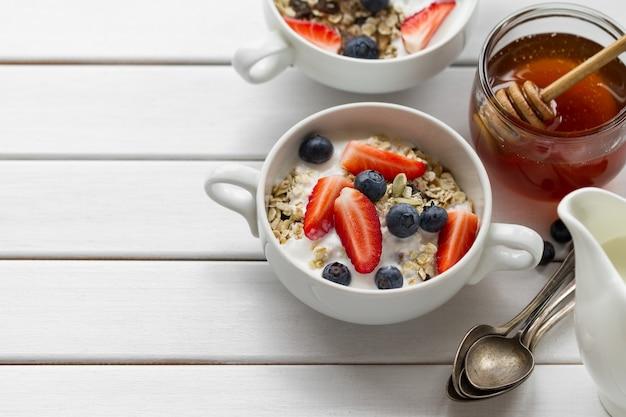 オーガニック、ヨーグルト、イチゴ、ブルーベリー、蜂蜜、ミルク、白い木製の背景に美味しいカラフルな朝食。上面図。 無料写真