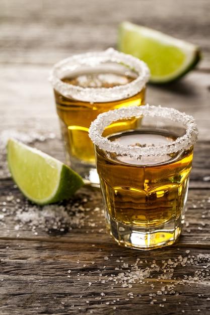 Вкусный алкогольный напиток коктейль текилы с известью и солью на фоне ярких деревянных столов. крупный план. Бесплатные Фотографии