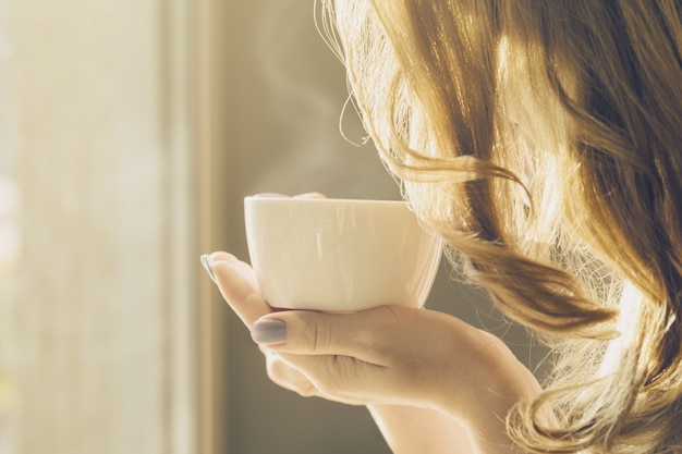 美しい女の子の若い女性はコーヒーを一人でコーヒーを飲む 無料写真