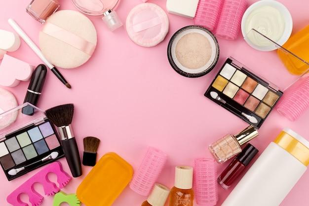 美容院フェミニンの概念。別のメイクアップ美容ケアエッセンシャルフラットレイピンクの背景に化粧品。上面図。上。 無料写真