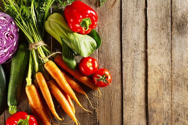 食品野菜のカラフルな背景。木製のテーブルにおいしい新鮮な野菜。コピースペース平面図 無料写真