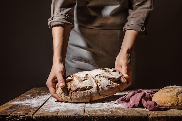 焼きたてのパンを保持しているパン屋さんやシェフ Premium写真