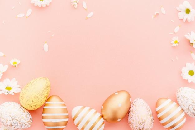 Пасхальная плоская кладка яиц с цветами на розовом Premium Фотографии